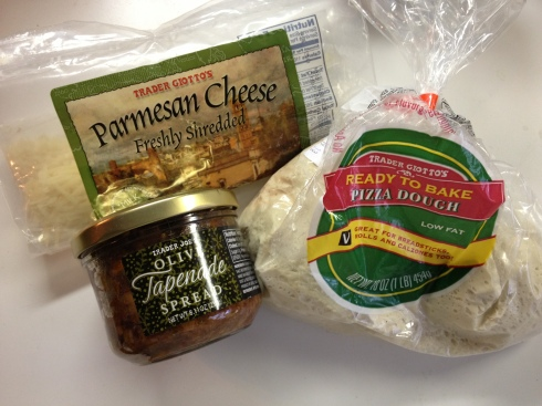 Parmesan cheese, a jar of tapenade and pizza dough